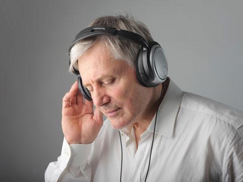 Zu sehen ist ein älterer Mann. Er trägt einen Kopfhörer und hat die Augen geschlossen. Entspannt aber auch konzentriert lauscht den Geräuschen, dabei hält er eine Hand an den Kopfhörer.