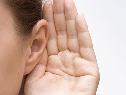 Das Foto zeigt ein Teilstück eines Frauengesichtes. Im Fokus steht ihr Ohr an das ihre Hand gehalten wird um zu lauschen oder besser zu hören.