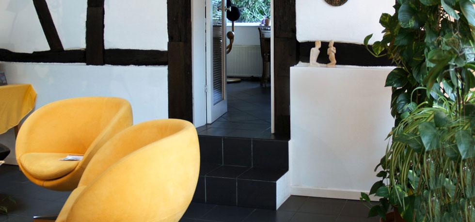 Hier kann man einen Teil der Praxisräume sehen, insbesondere den Wartebereich. Dort stehen zwei leuchtend gelbe Sessel, ein kleiner Tisch mit Zweitschriften und einige Pflanzen. Der Raum wirkt freundlich und hell.