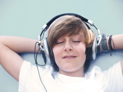 Ein Jungendlicher mit Kopfhörern liegt mit hinter dem Kopf verstreckten Armen auf dem Boden. Die Augen sind geschlossenen – mit einem leichtem Lächeln und lauscht er scheinbar der Musik. Er wirkt entspannt und scheint die Situation zu genießen.