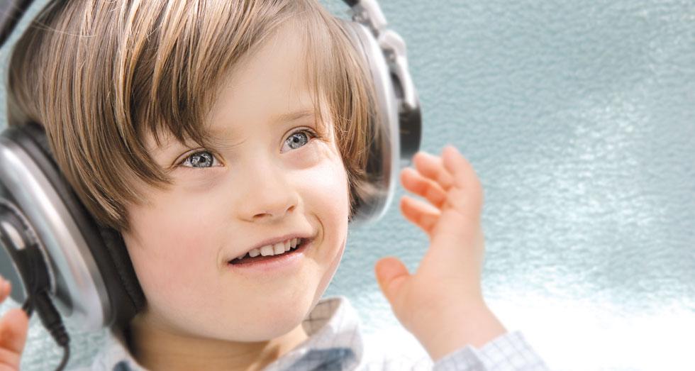 Das Foto zeigt einen kleinen Jungen im Alter von etwa 5 Jahren mit aufgesetztem Kopfhörer und angehobenen Händen in Richtung der Kopfhörer, fröhlich lächelnd und seitlich nach oben blickend. Daneben steht ein Text mit folgendem Inhalt: Zuhören lernen. Besser kommunizieren. Ausgeglichen handeln. Entwicklung fördern.