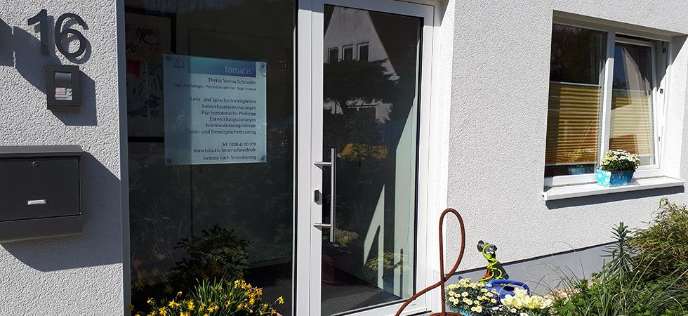 Im Bild zu sehen ist ein kleiner Ausschnitt des Gebäudes in dem sich die Praxis von Frau Schneider befindet. Mann kann eine Glashaustüre sehen. Im linken Fenster der Haustüre hängt ein Praxisschild. In blauer Schrift stehen unter dem Tomatis-Logo der Name von Frau Schneider und ihre Behandlungsschwerpunkte sowie Telefonnummer und Internetadresse.