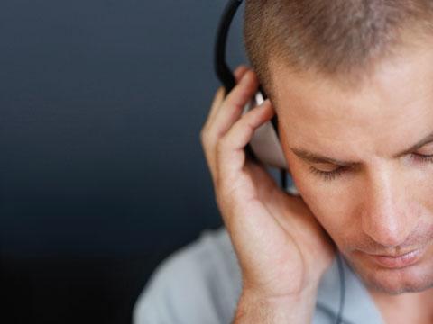 Ein junger Mann mit Kopfhörer auf dem Kopf und seiner rechten Hand am rechten Ohr. Er hat den Blick nach unten geschlagen und wirkt entspannt und aufmerksam.