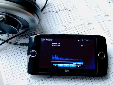 Im Bildmittelpunkt ist das Tomatis-Gerät SOLISTEN® zu sehen. Es sieht beinahe aus wie ein modernes Smartphone mit einem großen Display. Darauf kann man blaue Tastensymbole für einen CD-Player erkennen und ebenfalls in blau Balken, die wie Schwingungskurven aus der Akustik aussehen. Es ist ein Kopfhörer angeschlossen, der nur im Bildanschnitt erkennbar ist. Im Hintergrund liegen Blätter mit Diagrammen und eingezeichneten Kurven. Testergebnisse eines Hörtests.