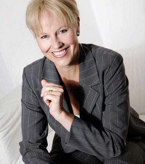 Zu sehen ist ein Foto von Frau Thekla Verena Schneider. Eine blonde, schlanke Frau mit modernem Hosenanzug. Sie lächelt freundlich in die Kamera.